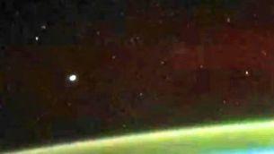 Un OZN misterios se îndreaptă spre aurora australă, fiind filmat de sus, de pe Staţia Spaţială Internaţională